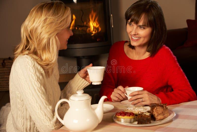 Mujeres que gozan de té y de la torta junto foto de archivo