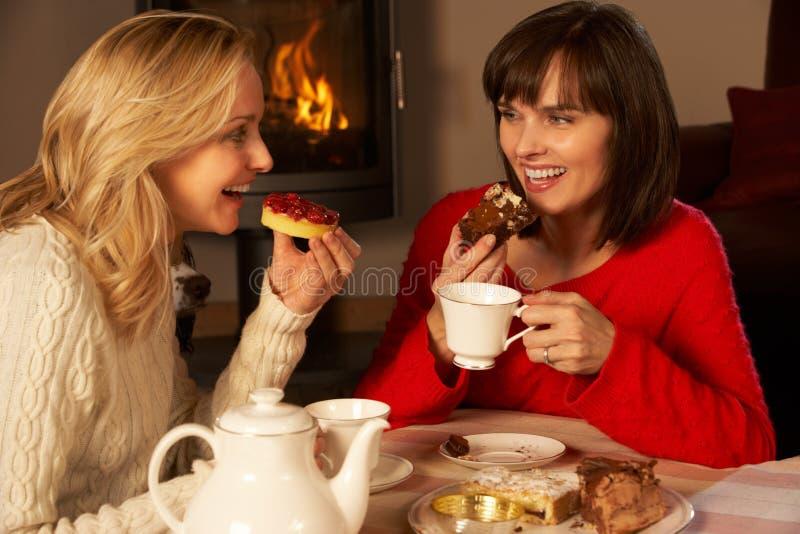 Mujeres que gozan de té y de la torta junto fotografía de archivo libre de regalías