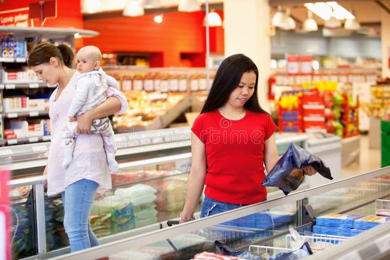 Mujeres que hacen compras en colmado imagen de archivo