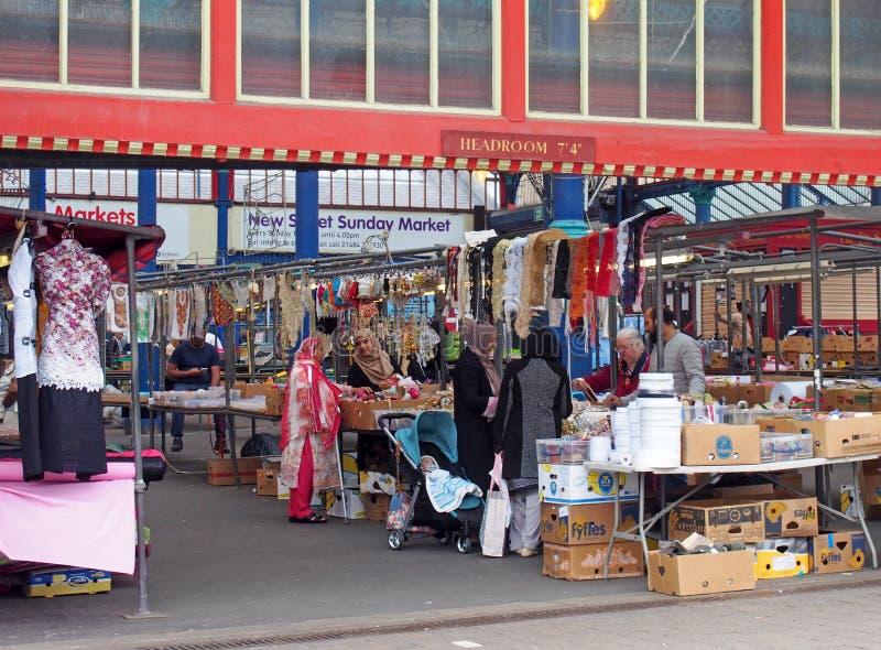 mujeres que hacen compras para la tela y los materiales de costura en una parada en el mercado de Huddersfield en West Yorkshire imagen de archivo libre de regalías