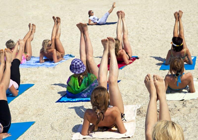 Mujeres que hacen ejercicio de la aptitud en una playa fotografía de archivo