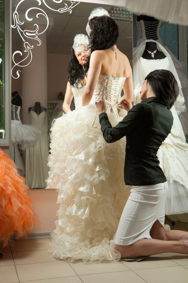 Mujeres que hacen el ajuste al vestido de boda imagen de archivo libre de regalías
