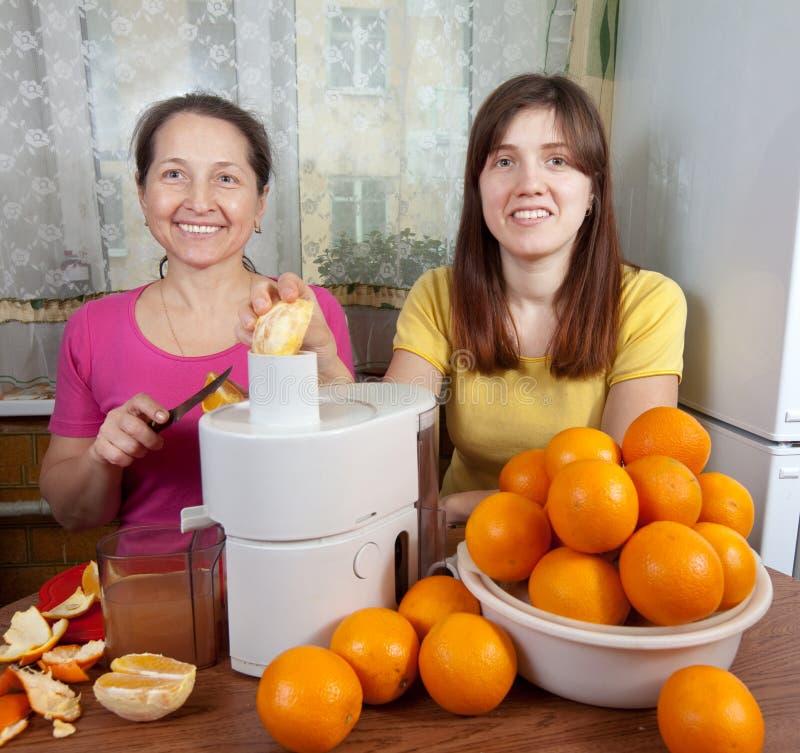 Mujeres que hacen el zumo de naranja fresco imagen de archivo