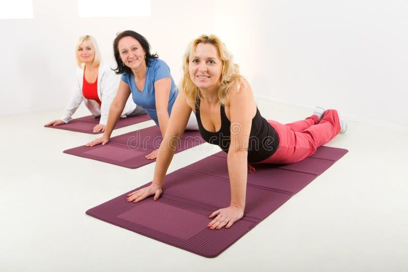 Mujeres que hacen exercices en la estera imágenes de archivo libres de regalías