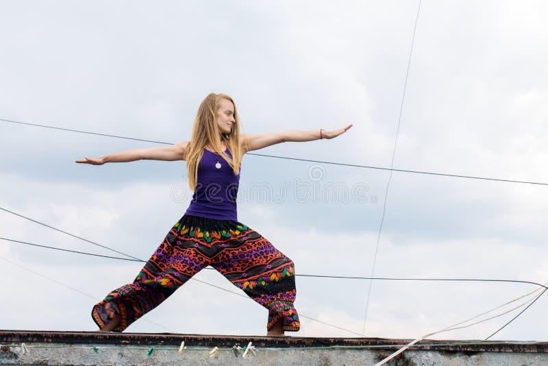 Mujeres que hacen la yoga, actitud del guerrero imagenes de archivo