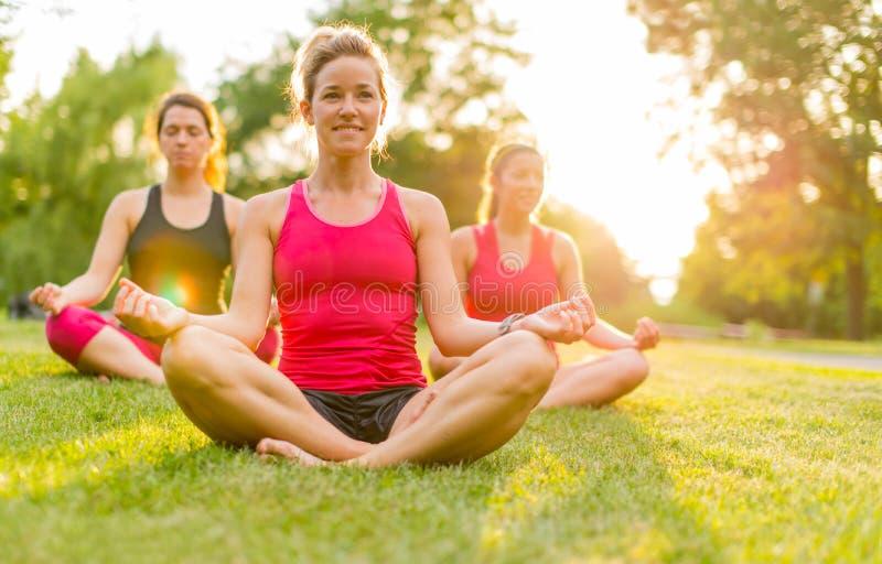 Mujeres que hacen yoga al aire libre en la puesta del sol imagenes de archivo