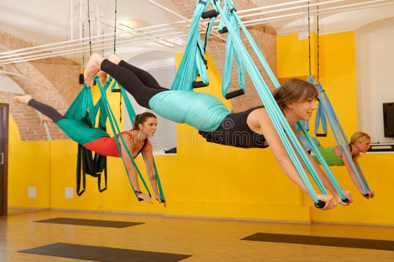 Mujeres que hacen yoga anti de la antena de la gravedad fotos de archivo
