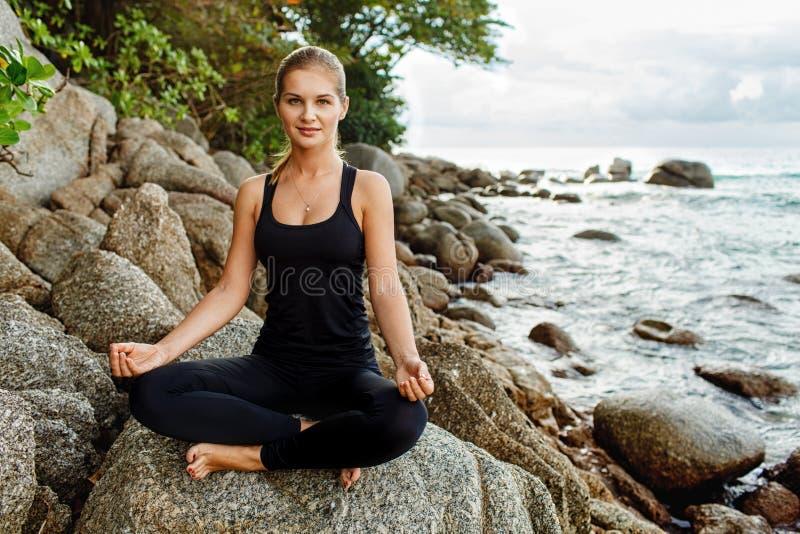 Mujeres que hacen yoga con el océano detrás imagen de archivo libre de regalías