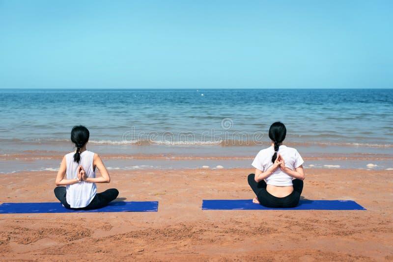Mujeres que hacen yoga en la playa fotos de archivo libres de regalías