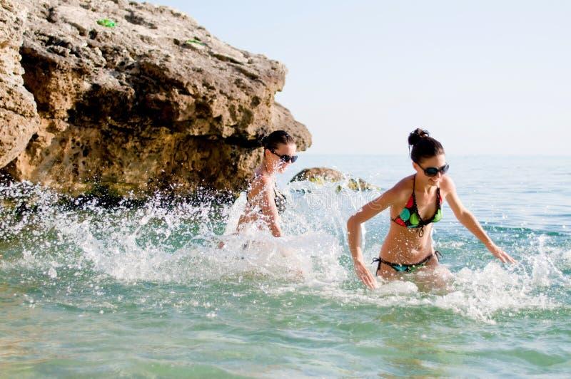 Mujeres que juegan en el mar imagen de archivo libre de regalías