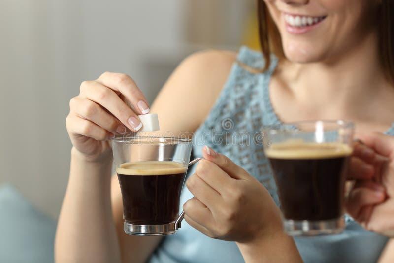 Mujeres que lanzan el azúcar en una taza de café fotos de archivo