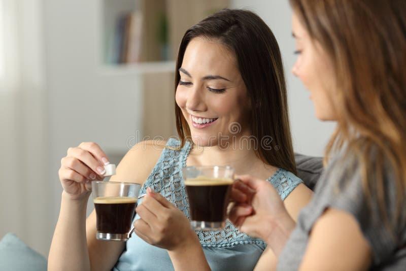 Mujeres que lanzan el cubo del azúcar en el café foto de archivo