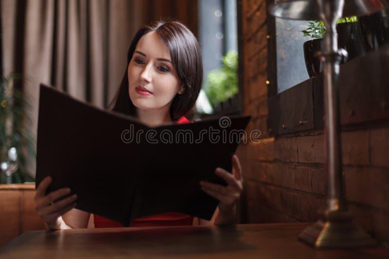 Mujeres que leen el menú. Mujeres de mediana edad hermosas que leen el menú en foto de archivo libre de regalías
