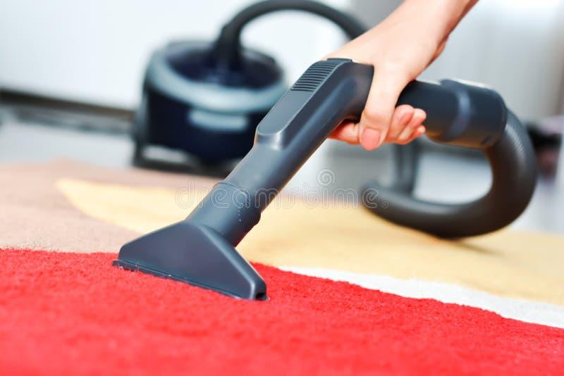 Mujeres que limpian una alfombra roja con un aspirador negro foto de archivo libre de regalías
