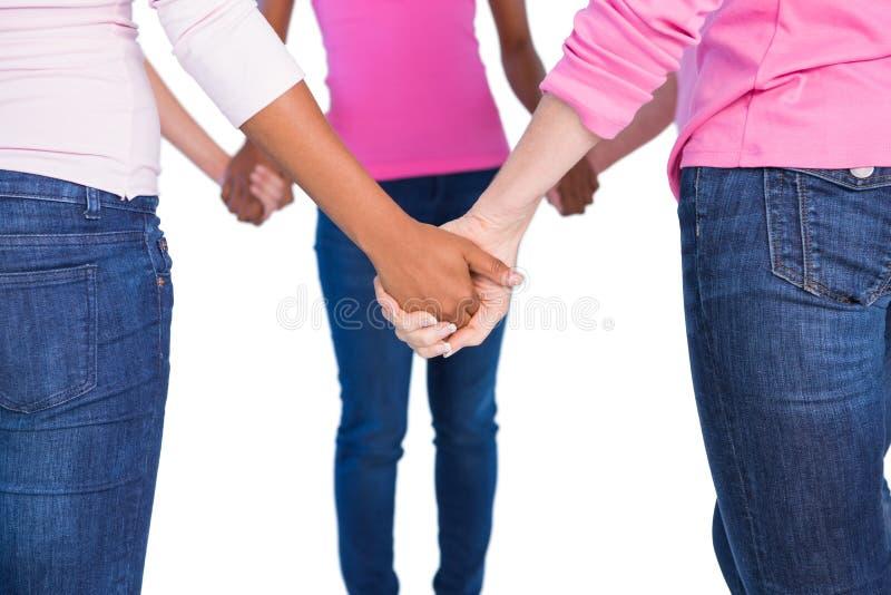 Mujeres que llevan el rosa para el cáncer de pecho que lleva a cabo las manos foto de archivo libre de regalías