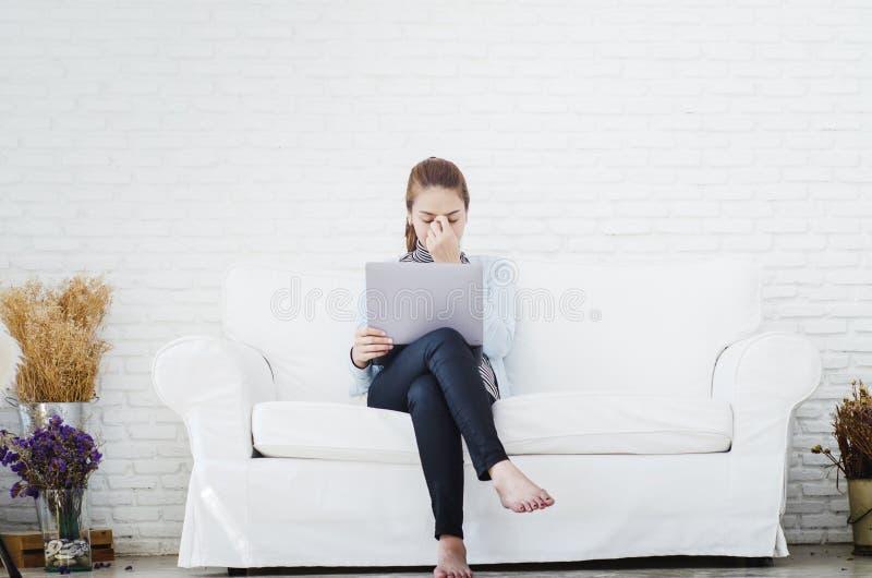 Mujeres que llevan las camisas azules que ella está trabajando y que las condiciones agotadoras imagen de archivo libre de regalías
