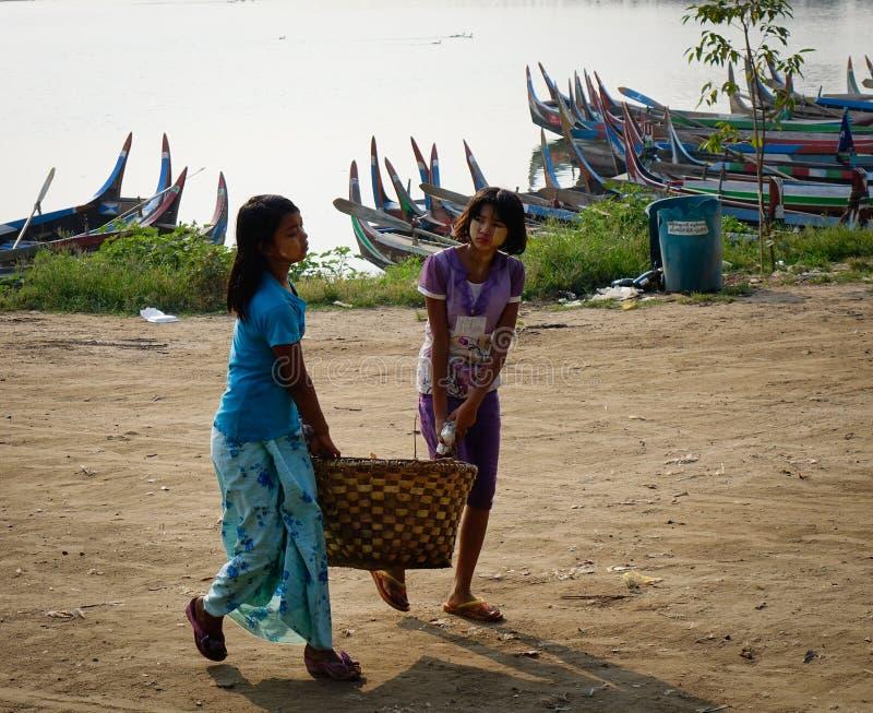 Mujeres que llevan mercancías en el camino rural en Mandalay, Myanmar imagen de archivo
