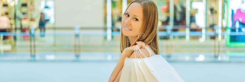 Mujeres que llevan muchos bolsos que hacen compras en la BANDERA borrosa del centro comercial, FORMATO LARGO imagenes de archivo