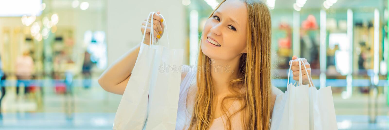 Mujeres que llevan muchos bolsos que hacen compras en la BANDERA borrosa del centro comercial, FORMATO LARGO imágenes de archivo libres de regalías