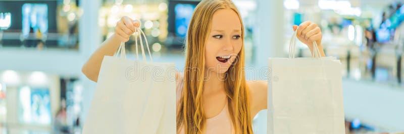 Mujeres que llevan muchos bolsos que hacen compras en la BANDERA borrosa del centro comercial, FORMATO LARGO fotografía de archivo