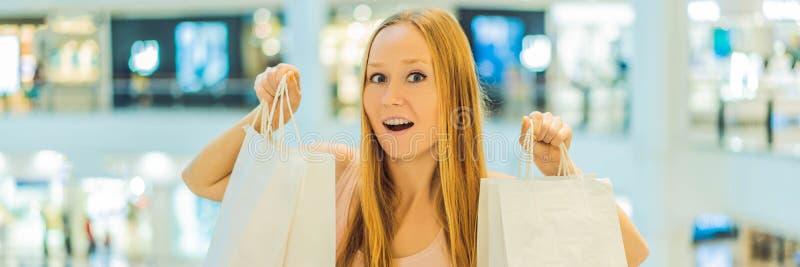 Mujeres que llevan muchos bolsos que hacen compras en la BANDERA borrosa del centro comercial, FORMATO LARGO fotos de archivo
