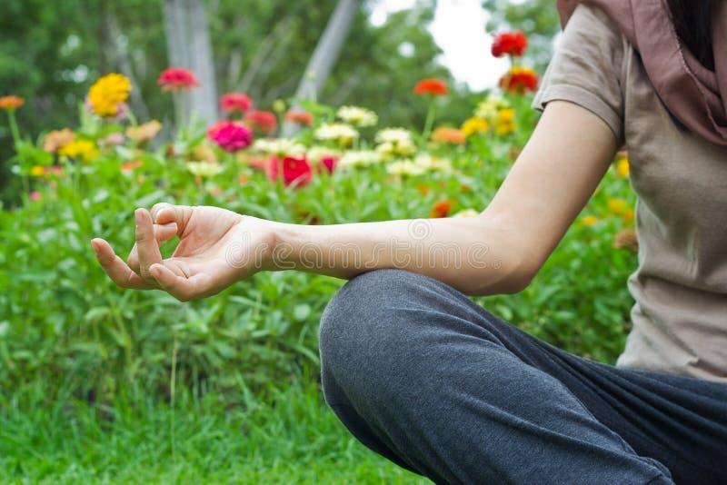 Mujeres que meditan al aire libre en fondo del parque de la flor foto de archivo libre de regalías