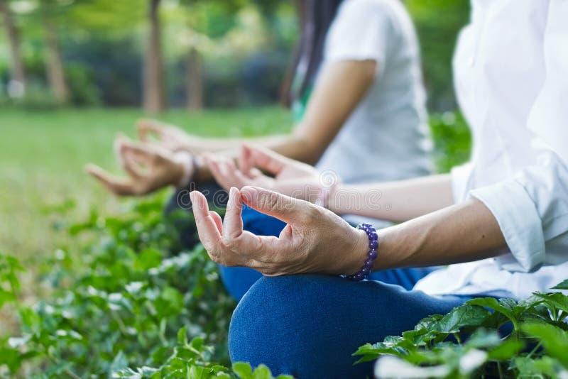 Mujeres que meditan al aire libre en parque verde en fondo de la naturaleza foto de archivo