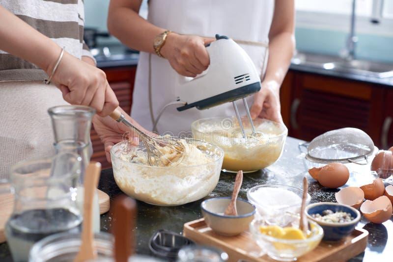 Mujeres que mezclan los ingredientes de la pasta imagen de archivo