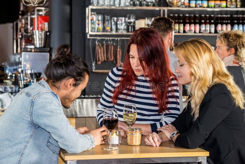 Mujeres que miran al amigo que usa el teléfono móvil en café foto de archivo libre de regalías