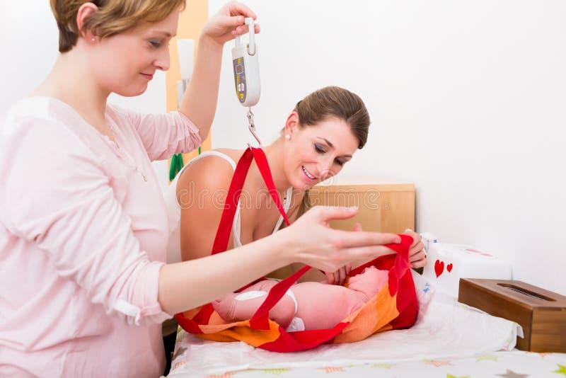 Mujeres que miran al bebé en el bolso de pesaje fotos de archivo libres de regalías