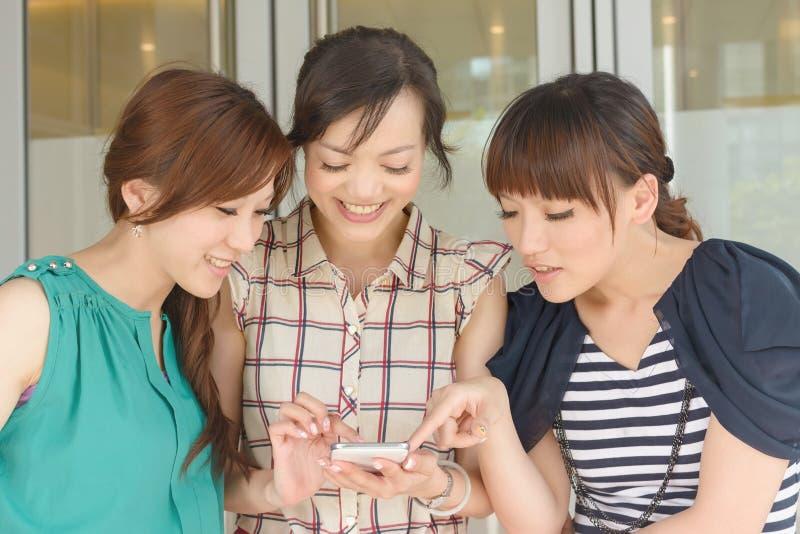 Mujeres que miran algo en un teléfono móvil imagen de archivo