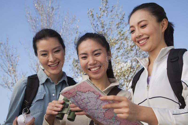 Mujeres que miran el mapa, sosteniendo los prismáticos imagen de archivo