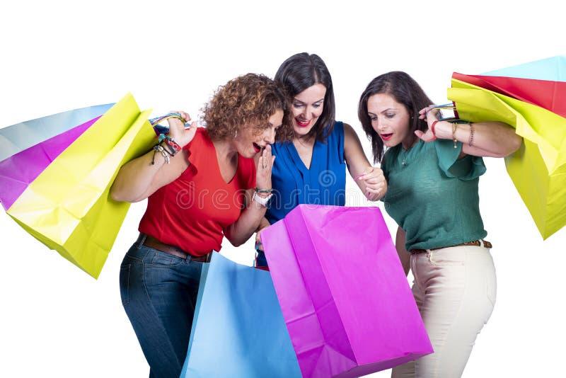 Mujeres que miran las compras dentro de los bolsos y asombrosamente en un fondo blanco imágenes de archivo libres de regalías