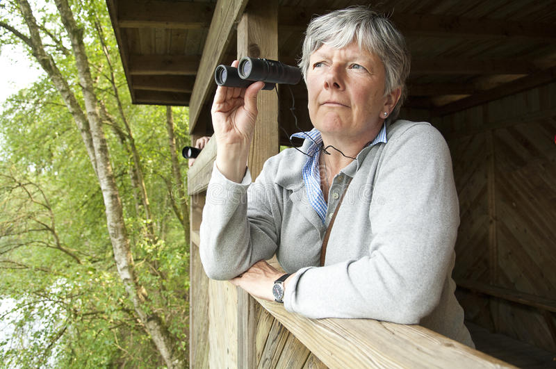 Mujeres que miran a través de los prismáticos imagen de archivo