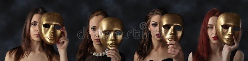 Mujeres que ocultan caras detrás de máscaras de oro fotos de archivo