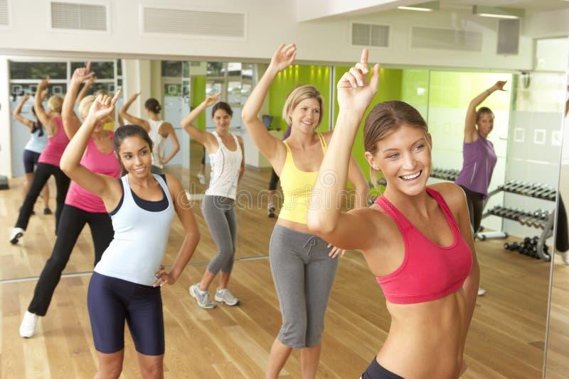 Mujeres que participan en la clase de Zumba en gimnasio imagen de archivo