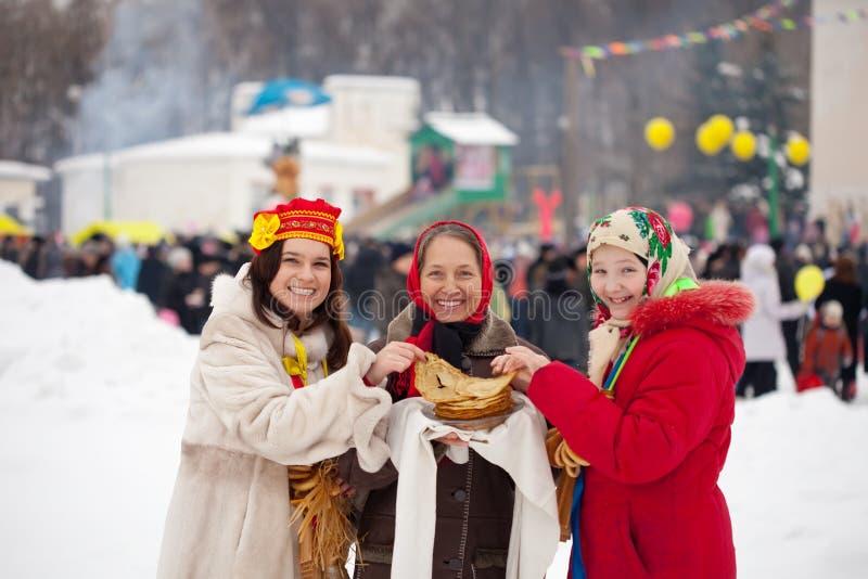 Mujeres que prueban la crepe durante Shrovetide fotos de archivo