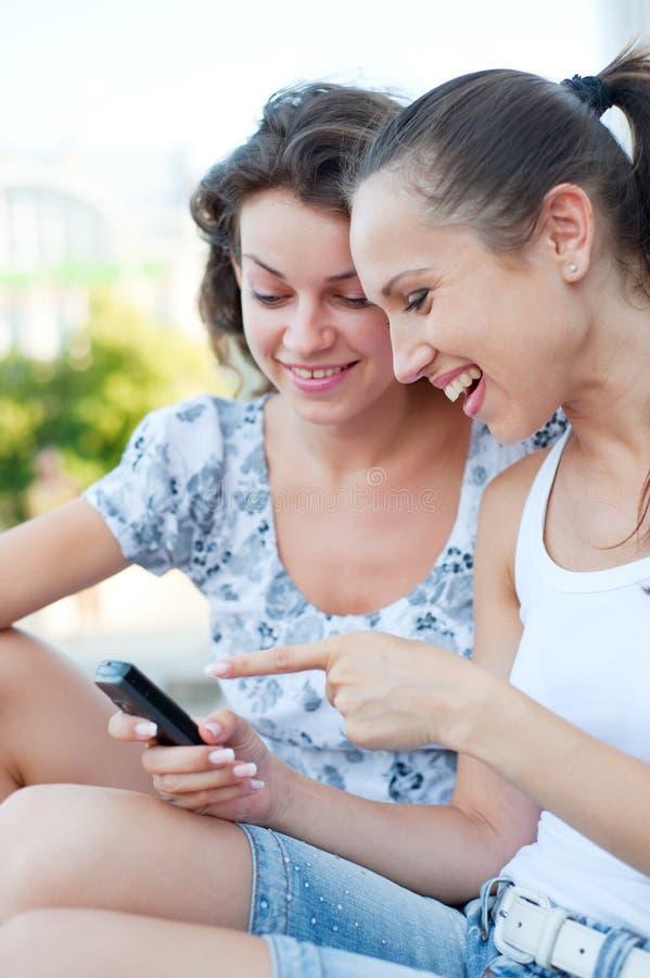 Mujeres que ríen y que miran el teléfono celular fotos de archivo libres de regalías