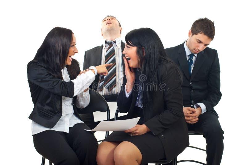 Mujeres que ríen y que señalan a los hombres dormidos foto de archivo libre de regalías