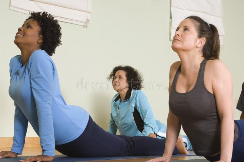 Mujeres que realizan yoga foto de archivo