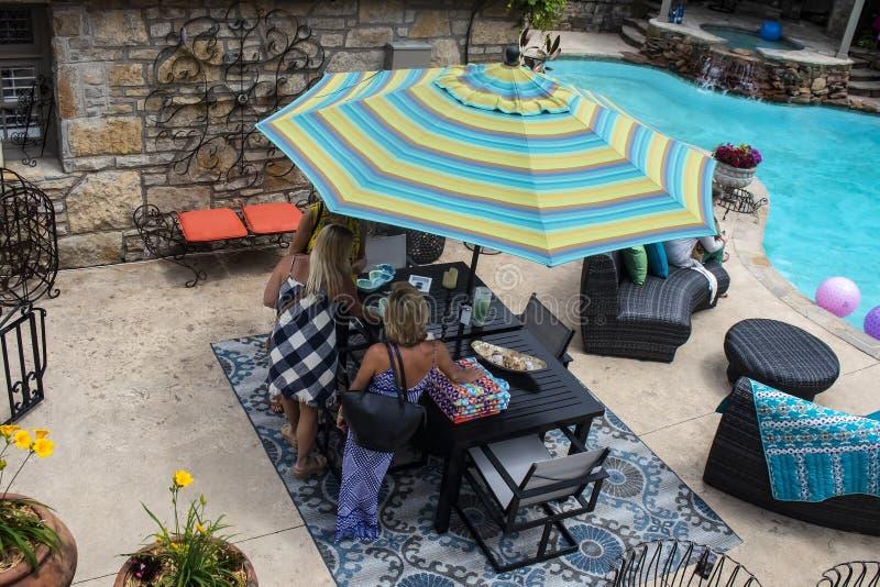 Mujeres que se colocan alrededor de la tabla de patio al lado de la piscina con los muebles al aire libre agradables - AUTORIZACI fotos de archivo