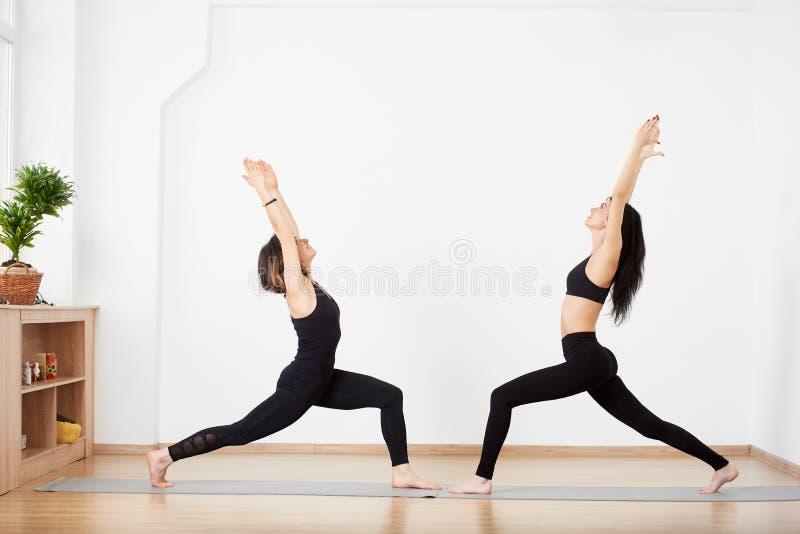 Mujeres que se colocan en la estera enfrente de uno a en la variación del guerrero que presento Clases amistosas de la yoga de la fotografía de archivo libre de regalías