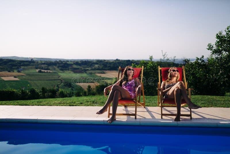 Mujeres que se relajan y que toman el sol en verano fotos de archivo
