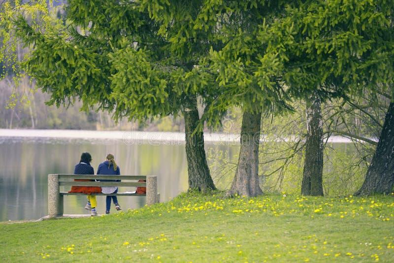 Mujeres que se sientan en el lago y hablar imagenes de archivo