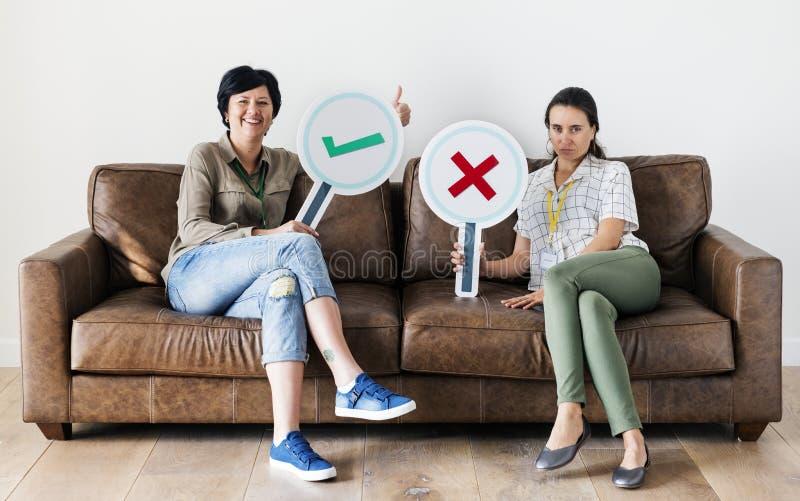 Mujeres que se sientan en el sofá que lleva a cabo iconos fotografía de archivo libre de regalías