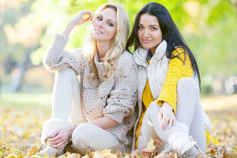 Mujeres que se sientan en parque del otoño imagenes de archivo
