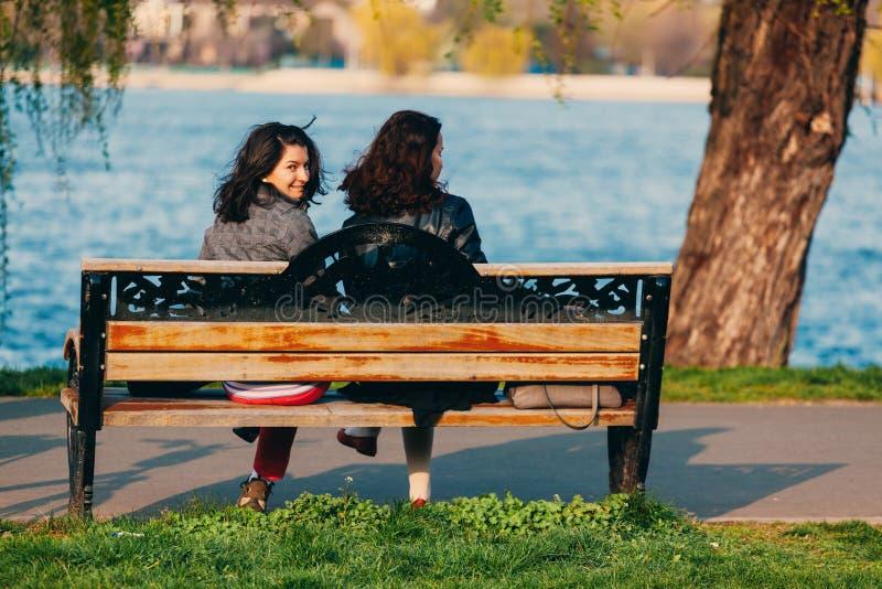 Mujeres que se sientan en un banco foto de archivo libre de regalías