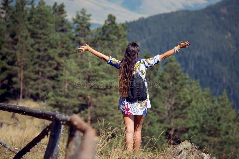 Mujeres que separan las sensaciones de las manos felices y mirada relajante en la montaña y el cielo imagen de archivo