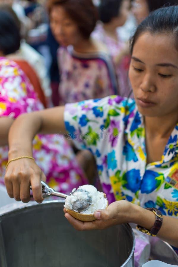 Mujeres que sirven la leche de coco del helado imagen de archivo