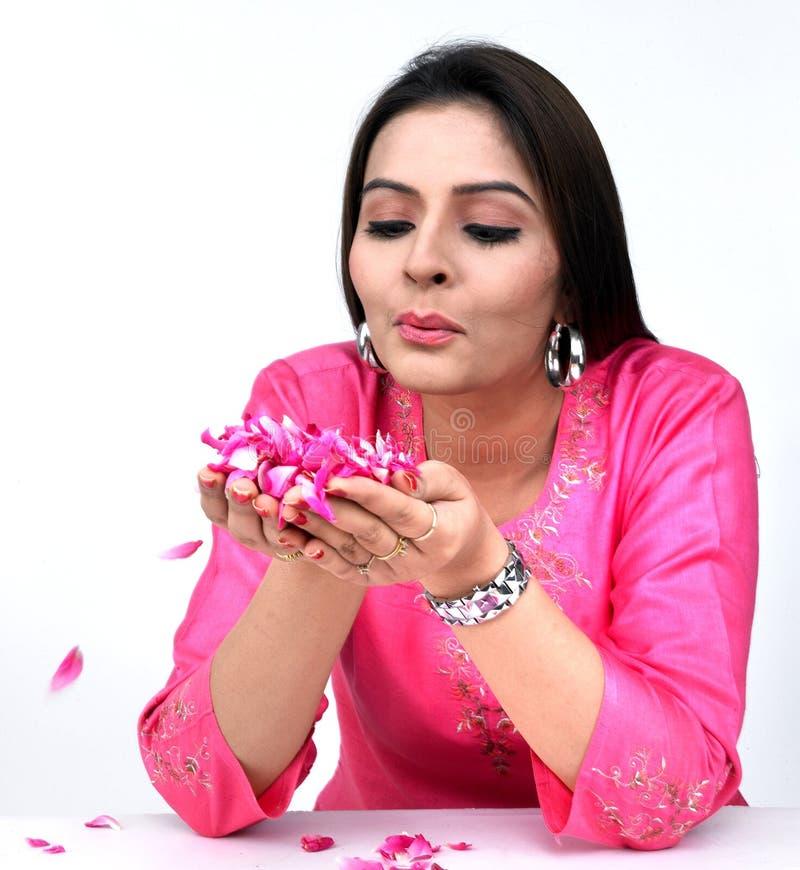 Mujeres que soplan los pétalos color de rosa imagen de archivo libre de regalías